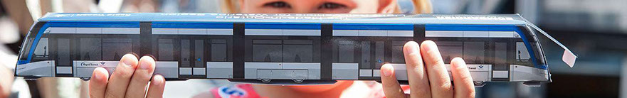 A little girl holds a model ION LRT vehicle.